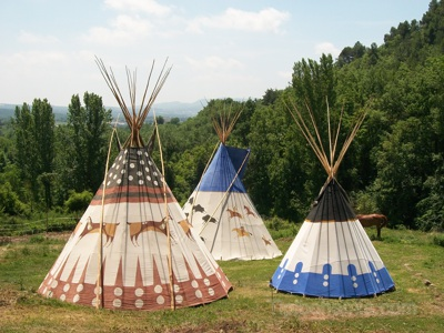 Three teepees of different  sizes, patterns and painting styles